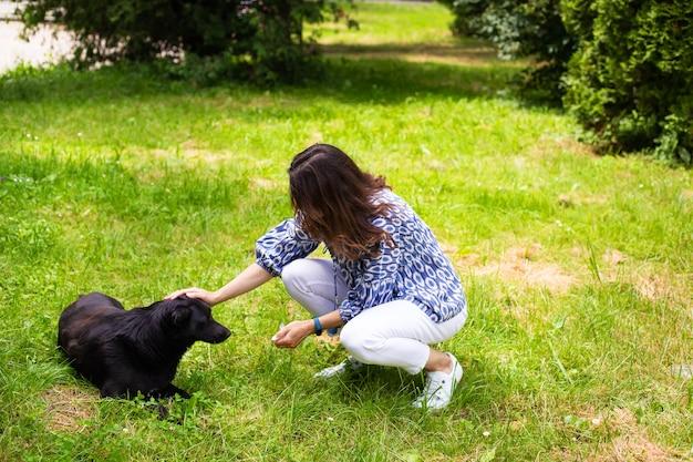 白いジーンズの若い女の子が通りで黒い犬と遊ぶ。アウトドアレクリエーション、犬と一緒に公園を散歩します。閉じる。