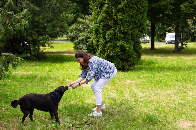 Молодая девушка в белых джинсах играет с черной собакой на улице.