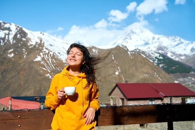 어린 소녀가 카즈벡 산을 바라보며 햇볕을 쬐고 있는 모닝 커피를 마시고 있습니다. 조지아 여행.