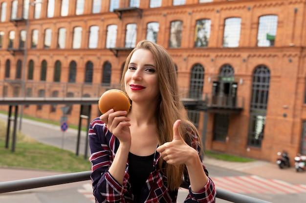 Молодая девушка ест свой гамбургер прямо на улице. она весело проводит время, наслаждаясь вкусной закуской.