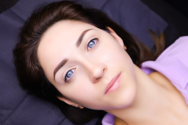 若い女の子が永久的な眉毛の化粧をした美容ソファに横たわっています