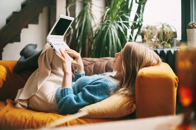 若い女の子がソファに横になって、ラップトップを膝に抱えて友達とテキストメッセージを送っています