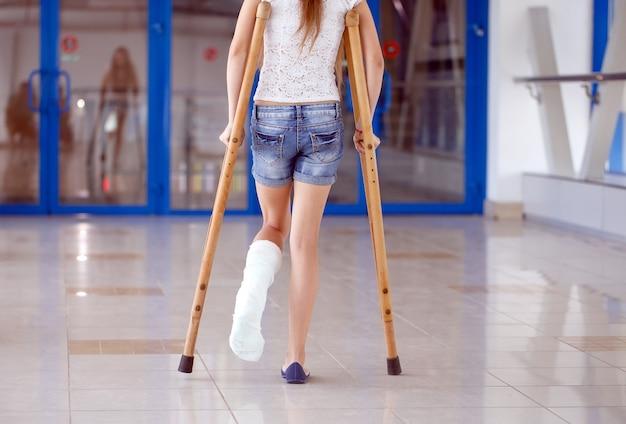 Молодая девушка на костылях в коридоре больницы.