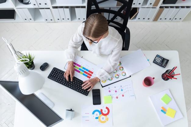 Молодая девушка сидит за столом в офисе, держит карандаш в руке и печатает на клавиатуре.