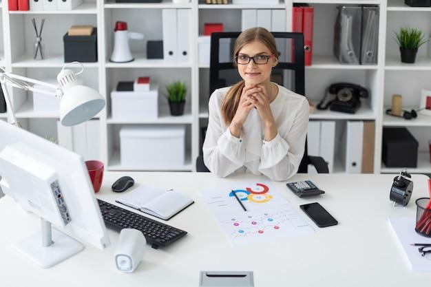 Молодая девушка сидит за компьютерным столом в офисе.