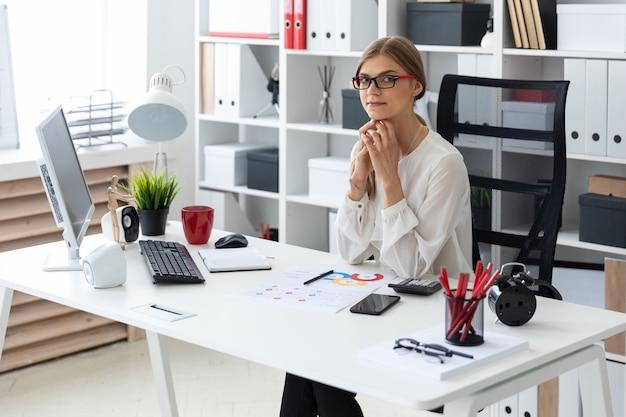 Молодая девушка сидит за компьютерным столом в офисе