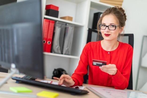 Молодая девушка сидит за столом в офисе, держит в руке банковскую карту и печатает на клавиатуре.