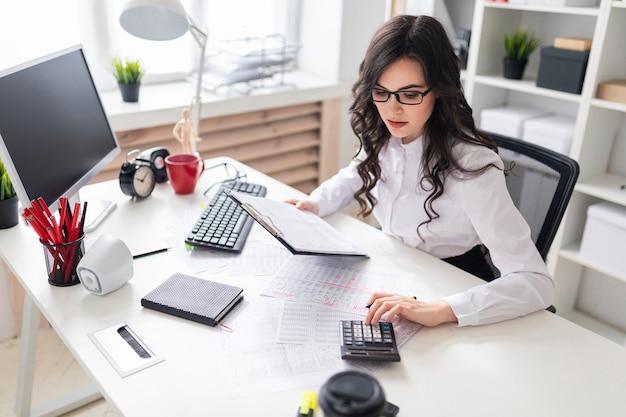 Молодая девушка сидит за офисным столом и благословляет калькулятор.
