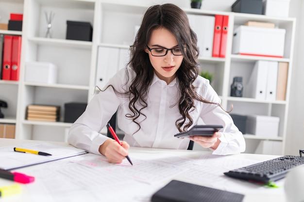 Молодая девушка сидит за офисным столом, работает с калькулятором и документами.