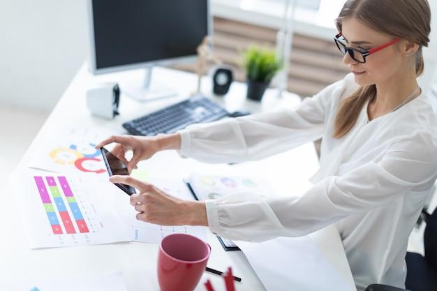 Молодая девушка сидит за столом в кабинете и фотографирует на телефонные карты.