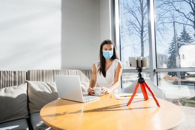 若い女の子がマスクのカフェに座って、ビデオブログをリードしています。カメラへの通信。