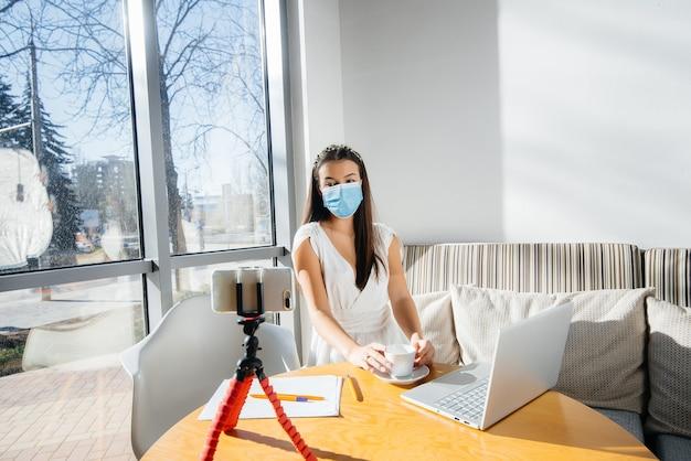 Молодая девушка сидит в кафе в маске и ведет видеоблог