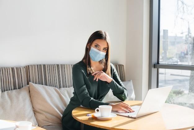 어린 소녀가 마스크를 쓰고 컴퓨터에서 일하는 카페에 앉아있다.