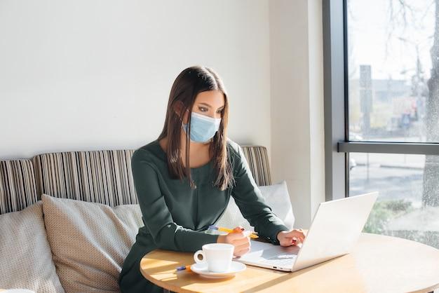 若い女の子がマスクをかぶってカフェに座って、コンピューターで働いています。