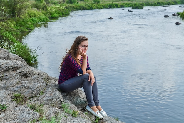 Молодая девушка сидит на камне у реки