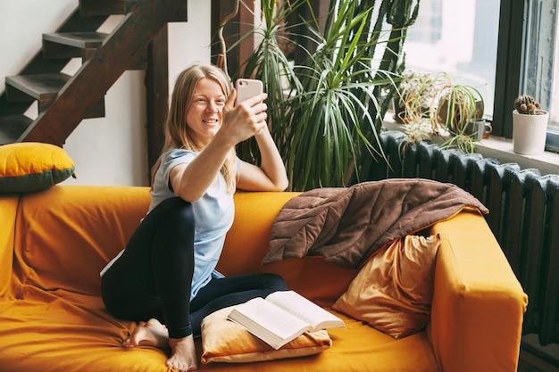Молодая девушка сидит на диване и делает селфи на свой телефон
