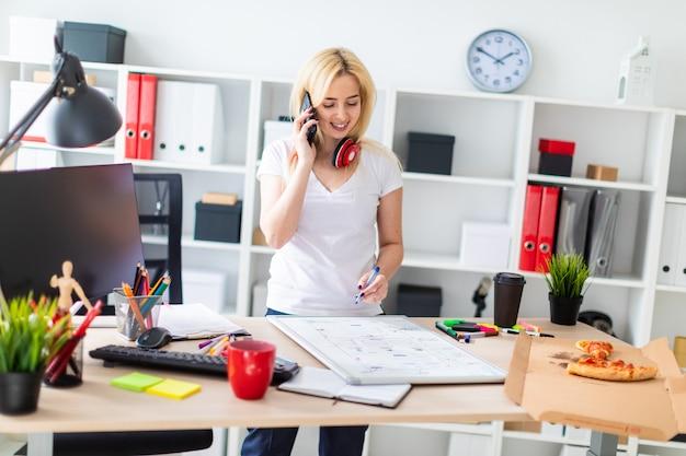 Молодая девушка стоит возле стола, разговаривает по телефону и держит маркер в руке. на столе магнитная доска. на шее у девушки висят наушники.