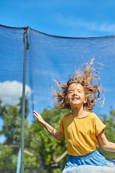 Молодая девушка прыгает на батуте на открытом воздухе, на заднем дворе дома в солнечный летний день, летние каникулы.
