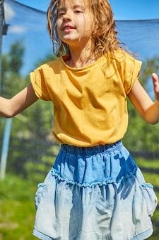 Молодая девушка прыгает на батуте на открытом воздухе в солнечный летний день на заднем дворе