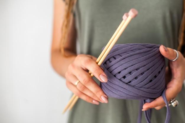 緑のドレスを着たドレッドヘアを持つ少女の編み物は、紫の糸のかせと編み物用の木製の編み針を持っています。明るい背景。