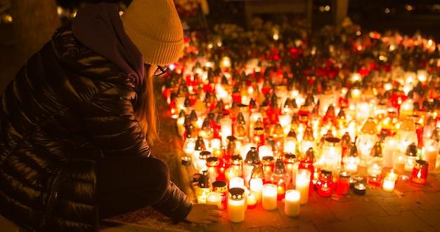 어린 소녀가 모든 성인의 날에 촛불을 켭니다.