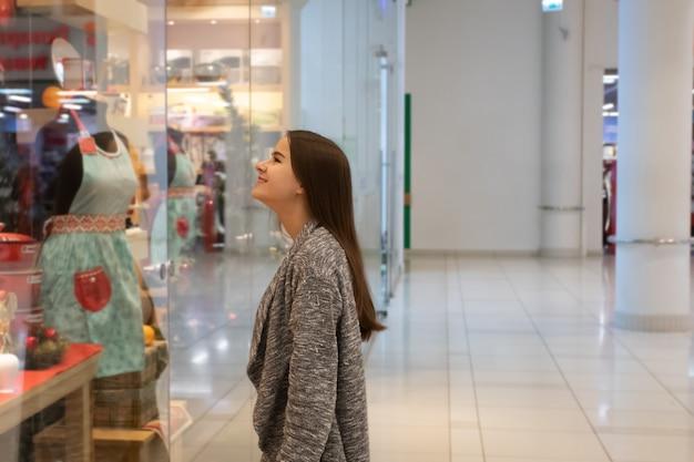 Молодая девушка смотрит на витрины магазина, выбирает подарки в торговом центре