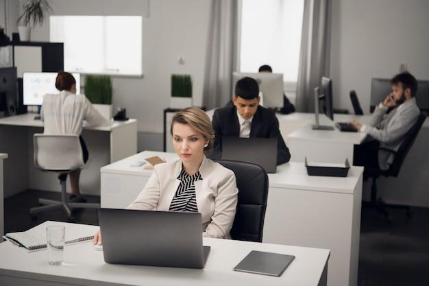 ラップトップを持った作業服のコードでオフィスにいる若い女の子のマネージャーは、会社のクライアントと通信します。