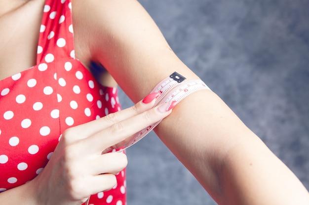 Молодая девушка измеряет бицепс лентой