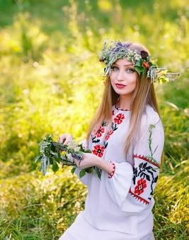 真夏に野生の花の花輪を持つスラブの外観の少女。