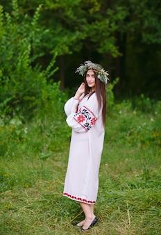 Молодая девушка славянской внешности с венком из полевых цветов в середине лета.