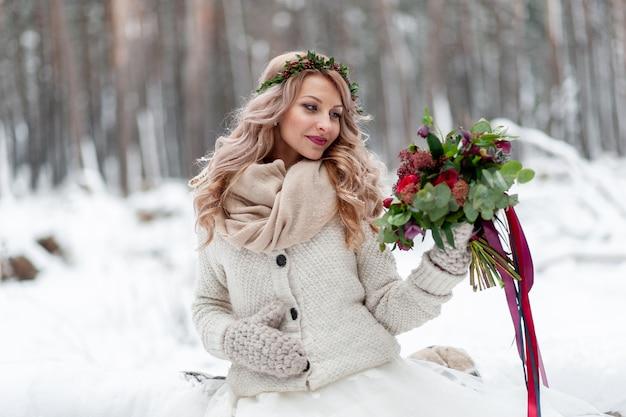Молодая девушка славянской внешности с венком из полевых цветов. красивая белокурая невеста держит букет в предпосылке зимы.