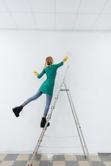 Stepladder에 어린 소녀는 롤러로 흰 벽을 그립니다. 내부 수리.