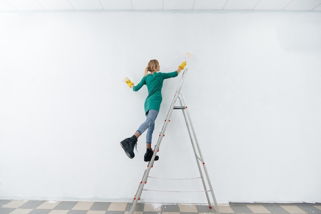 접사 다리에 어린 소녀가 롤러로 흰 벽을 칠합니다.
