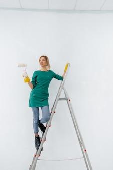 사다리 위에 있는 어린 소녀가 롤러로 흰 벽을 칠하고 있다