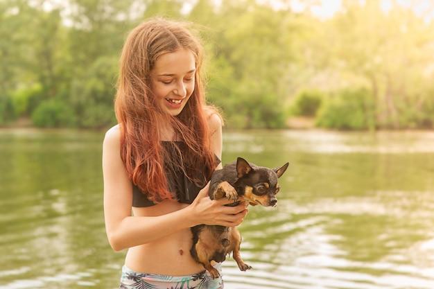 Молодая девушка на реке с чихуахуа в руках. летняя концепция.