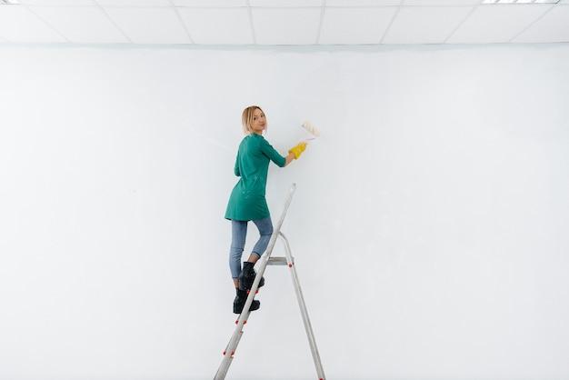 계단에서 어린 소녀가 롤러로 흰 벽을 칠합니다.