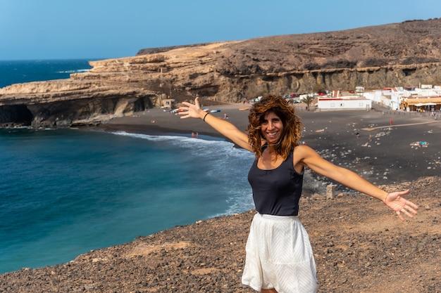Молодая девушка на отдыхе на пляже аджуй, пахара, западное побережье острова фуэртевентура, канарские острова. испания