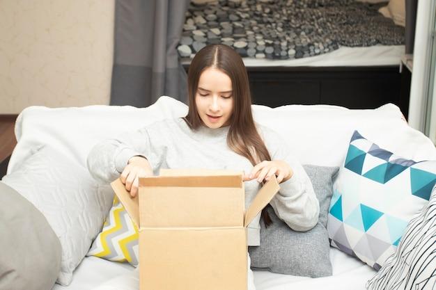 Девушка открывает подарок, полученный по почте, в картонной коробке