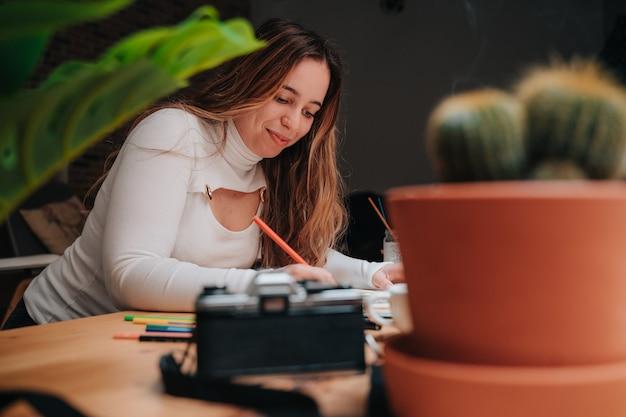 Молодая девушка рисует мандалу цветными карандашами на деревянном столе. у нее есть кисти, благовония, фотоаппараты и большое окно.