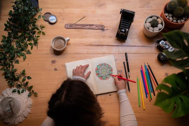 Молодая девушка рисует мандалу разноцветными карандашами на деревянном столе. у нее есть кисти, благовония, фотоаппараты и большое окно. вид сверху.