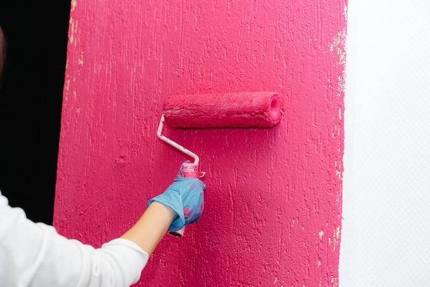 Молодая девушка красит белую стену в розовый цвет крупным планом с роликом. ремонт интерьера.