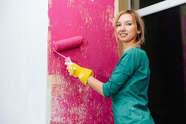 어린 소녀가 롤러 클로즈업으로 분홍색으로 흰 벽을 그립니다.