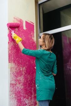 롤러 클로즈업으로 흰 벽을 분홍색으로 칠하는 어린 소녀