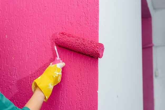 Молодая девушка красит белую стену в розовый цвет крупным планом с роликом