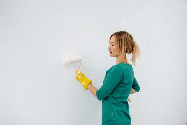롤러로 흰 벽을 칠한 어린 소녀