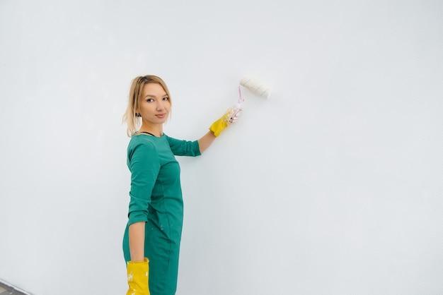 어린 소녀가 롤러로 흰 벽을 칠하고 있다