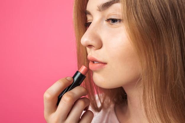 Молодая девушка красит губы помадой и смотрит в зеркало, на розовую стену