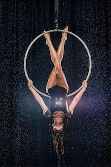 若い女の子が空中リングでアクロバティックな要素を実行します。黒地にアクアスタジオ撮影公演。