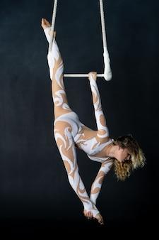 若い女の子が空中台形でアクロバティックな要素を実行します