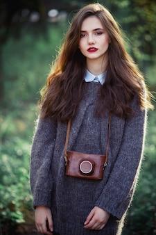Молодая девушка-фотограф с длинными темными волосами и яркими губами в теплом шерстяном свитере со старым пленочным фотоаппаратом в кожаном футляре на шее стоит на фоне леса на закате.